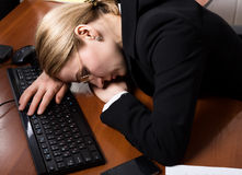Pretty business woman in a business suit sleeping on computer keyboard Royalty Free Stock Photos