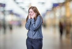 Pretty business woman covering her ears over blur background. Stock Photography
