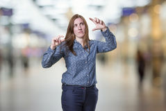 Pretty business woman doing tiny and big sign over blur background. Pretty business woman doing tiny and big sign over blur background Royalty Free Stock Photography
