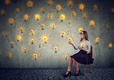 Pretty business woman juggling with light bulbs stock image
