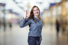 Pretty business woman making ok gesture over blur background Royalty Free Stock Photos