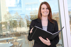 Pretty Business Woman at office. Holding a notebook stock photography