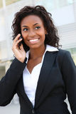 Pretty Business Woman on Phone. Pretty african americanl business woman talking on her mobile phone at office building Stock Photo