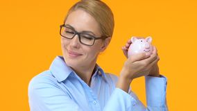 Pretty business woman shaking piggy bank, favorable credit terms, low interest