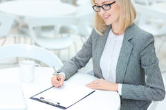 Pretty business woman signing papers Stock Images