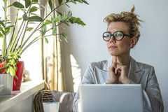 Pretty  business woman sits pensively with a laptop near the window. Stock Photography