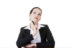 Pretty business woman in sitting at the desk and thinking Royalty Free Stock Photography