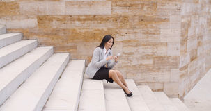 Pretty business woman sitting on steps using phone Stock Photo