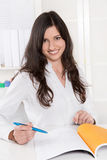 Pretty business woman smiling at desk in her office Royalty Free Stock Photos