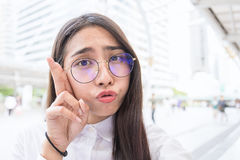 Pretty business woman take a self portrait with her smart phone outside. Asian nerdy glasses girl selfie over building background Royalty Free Stock Photos