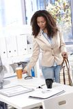 Pretty businesswoman arriving at office. Pretty afro-american businesswoman arriving at office, having coffee stock photo