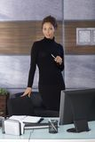 Pretty businesswoman in black in office Royalty Free Stock Photo