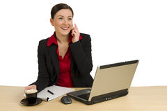 Pretty businesswoman calling behind desk. Beautiful youg woman with mobile phone behind her desk, on white Royalty Free Stock Photo