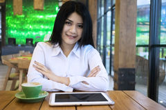 Pretty businesswoman with coffee and tablet in cafe Royalty Free Stock Photos