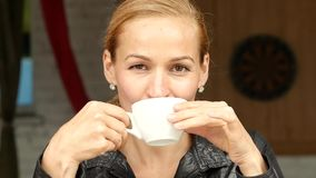 Attractive businesswoman drinking coffee and relaxing in outdoor cafe on summer terrace. slow motion stock video