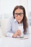 Pretty businesswoman drinking milk at her desk Stock Image