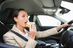 Pretty businesswoman having doughnut while driving Royalty Free Stock Photo