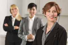 Pretty Businesswoman with Headset and Colleagues Stock Images