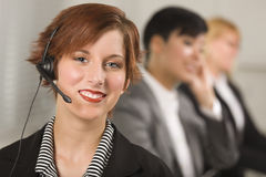 Pretty Businesswoman with Headset and Colleagues Royalty Free Stock Image