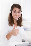 Pretty businesswoman with headset sitting at desk with giving th Stock Photos