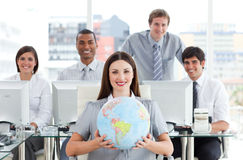 Pretty businesswoman and her team. Showing a terrestrial globe in the office royalty free stock image