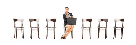 Pretty businesswoman holding a briefcase and waiting for job int Stock Images