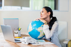 Pretty businesswoman holding globe Royalty Free Stock Image