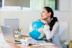 Pretty businesswoman holding globe Royalty Free Stock Image
