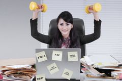 Pretty businesswoman lifting two dumbbells Royalty Free Stock Photography