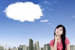 Pretty businesswoman looking at empty cloud Stock Photography