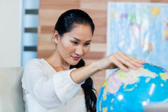 Pretty businesswoman looking at globe Stock Photo