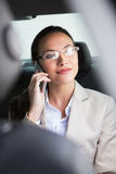 Pretty businesswoman making a phone call. In her car Stock Image