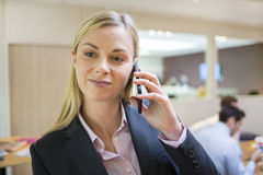 Pretty businesswoman at mobile phone, meeting colleague backgrou Stock Photos