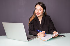 Pretty Businesswoman in the office on the phone, headset, in call center and make notice. Pretty Businesswoman in the office on the phone, headset, Skype stock images