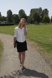 Pretty businesswoman in the park; on the phone Stock Image