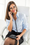 Pretty Businesswoman Phoning. A young pretty businesswoman with glasses sitting in the office chair and phoning, holding the phone in her lap, smiling looking at Royalty Free Stock Photography