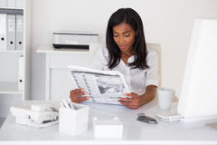 Pretty businesswoman reading newspaper at her desk Royalty Free Stock Images