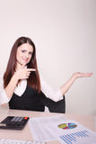 Pretty businesswoman showing thumb up to camera at her desk in h Royalty Free Stock Photos