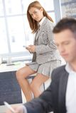 Pretty businesswoman sitting on desk texting Royalty Free Stock Images