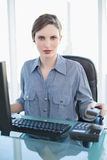 Pretty businesswoman sitting at her desk replacing the receiver Stock Photo