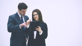 Pretty businesswoman standing with tablet in her hands, explaining something to her partner. Businessman on her side is