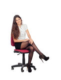 Pretty businesswoman in a stylish miniskirt sitting. Isolated on white Royalty Free Stock Photos
