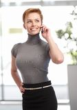 Pretty businesswoman talking on mobile. Pretty young businesswoman talking on mobilephone at office building Royalty Free Stock Photos