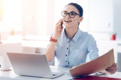 Pretty businesswoman talking on phone and getting excited during conversation. Such a nice idea. Young up and coming brunette holding an envelope with documents royalty free stock image