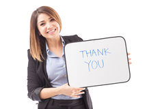 Pretty businesswoman with a THANK YOU sign. Portrait of a gorgeous young Hispanic businesswoman holding a small whiteboard with the text THANK YOU on it Royalty Free Stock Photo