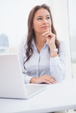 Pretty businesswoman thinking at her desk Stock Photos