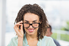 Pretty businesswoman tilting her reading glasses Royalty Free Stock Photography