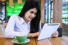 Pretty businesswoman using tablet in cafe Stock Image