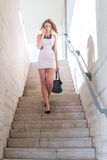 Pretty businesswoman walk on the stairs Stock Photo