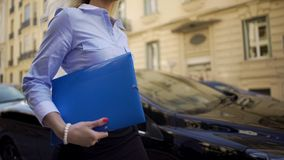 Pretty businesswoman walking along street to office, holding documents folder royalty free stock photo